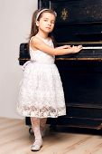 5 year old girl in a black dress sitting near the piano