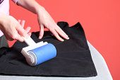 pic of lint  - Woman hand cleaning dust with lint roller - JPG