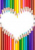Colored pencils in a heart shape. isolated on white background