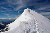 stock photo of descending  - Climber descending snowy peak at high mountains - JPG
