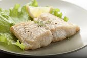 pic of pangasius  - Fried fillet of pangasius with lettuce and lemon on the green plate - JPG