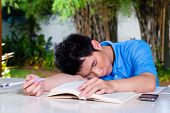 Young Chinese Asian student is bored at home with difficult homework assignment for school next day, he has fallen asleep