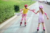 stock photo of elbows  - Two girls in roller skates - JPG