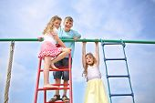 Three cheerful children at the top of playground equipment