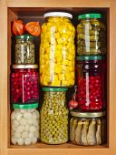 many glass bottles with preserved food in wooden cabinet