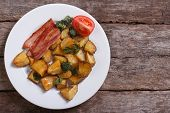 Fried potato with bacon and vegetables