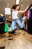 Beautiful happy brunette girl with shopping bag jumping in a sport outlet