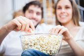 stock photo of watching movie  - Young couple eating popcorn while watching a movie - JPG
