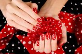 Close up on beautiful female hand with cute red manicure with white dots.