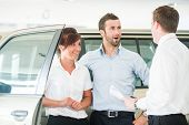 Happy couple in car salon with car salesman