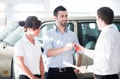 Salesman handing car keys to couple of buyers