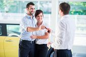 Smiling couple getting car keys from a salesman at dealership