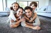 stock photo of daddy  - Family at home relaxing on carpet - JPG