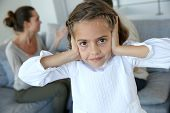Little girl covering her ears not to hear parents arguing