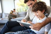 stock photo of indoor games  - Father and son playing with digital tablet - JPG