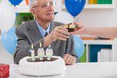 Smiling senior man receiving birthday gift, celebrating 100th birthday