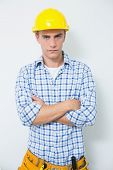 Portrait of a serious handyman in yellow hard hat with arms crossed against white background