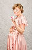 foto of gullible  - Embarrassed pregnant woman in dress holding contraceptives - JPG