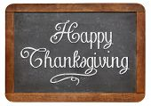 Happy Thanksgiving - white chalk handwriting on a vintage slate blackboard isolated on white