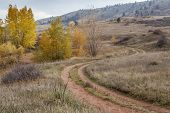 nostalgic autumn scenery - dirt road meandering through Colorado foothills with last foliage color n
