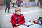 Beautiful Toddler Boy In Red Clothes On Flea Market.