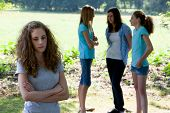image of ignorant  - Sad young teenage girl standing with folded arms as her teenage peers ignore her and stand in a group chatting conceptual of a social outcast - JPG