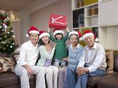 pic of grandpa  - Home portrait of an Asian family with Christmas hats and gifts - JPG
