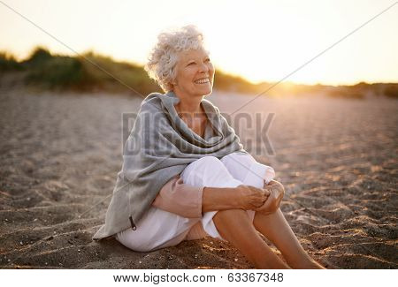 Cheerful Old Woman Sitting On The Beach poster