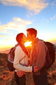 Kissing couple - romantic lovers hiking at sunset sharing kiss enjoying sunshine and love on beautif
