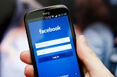 Hand Holding Smartphone With Facebook Social Network Mobile App With English Interface