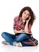 Student girl with bag sitting on floor and talking on cell phone