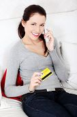 Beautiful woman is holding credit card and talking to the phone, shopping on the phone concept. Indo