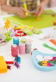 image of thread-making  - Closeup on threads and buttons on table and young woman making easter decoration in background - JPG