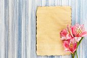 Beautiful Alstroemeria flowers and empty sheet on wooden table