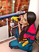 Woman  builder fixing heating system with special tool.