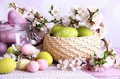 Composition with Easter eggs in glass jar and wicker basket, and blooming branches on light backgrou