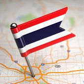 Thailand Small Flag on a Map Background.
