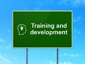 Education concept: Training and Development and Head With Lightbulb on road sign background