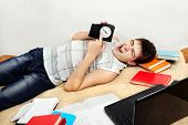 picture of yawning  - Tired Student Yawning on the Sofa and pointing on the Clock - JPG