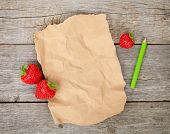 Blank paper with copy space and ripe strawberries over wooden table backgroun