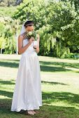 Full length of young bride smelling flowers in park
