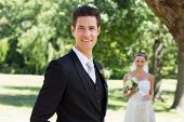 Portrait of confident groom with bride standing in background at garden