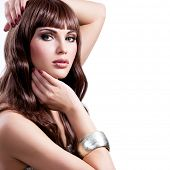 Portrait of a beautiful young woman with long brown hairs. Pretty girl model with stylish bijouterie of silver color.