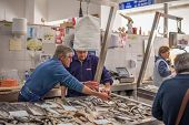 ALBUFEIRA, PORTUGAL  APRIL 06, 2014: Photo showing fish sellers in a traditional fish market that ta