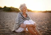stock photo of shoreline  - Happy retired woman wearing shawl sitting relaxed on sand at the beach - JPG