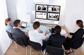stock photo of angle  - High Angle View Of Businesspeople In Video Conference At Business Meeting - JPG