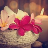 Spa still life setting with aromatic candles, frangipani flower, cold and hot stones in vintage retro style.