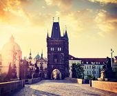 Vintage retro hipster style travel image of Charles bridge tower in Prague on sunrise, Czech Republi