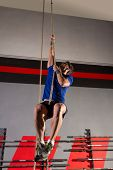 Rope Climb exercise man workout at gym climbing
