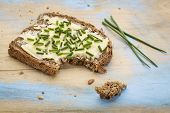 a slice of rye bread with butter and chive on painted cutting board